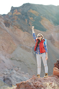 Modern girl in fashionable tourist gear standing on top of peak in mountains raising hand up, inspired and enjoying her freedom