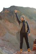 Motivational image of young handsome traveler wearing fashionable clothes standing on top of peak in mountains raising hand up in excitement and smiling, enjoying his freedom