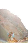 Rear view of tourist couple with big backpacks holding hands at hike in mountains, wide shot in bright sunlight