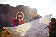 Travelling couple, young man and woman, stopping to look at map with directions during mountain hike in bright sunlight