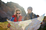 Tourist couple, young man and woman, stopping to look at map with directions during mountain hike in bright sunlight