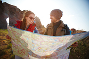 Joyful travelers, young man and woman, taking a hike through mountains in bright sunlight, stopping to look at huge map with directions