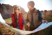 Lens flare image of smiling young couple, man and woman, looking at each other while holding big map at hike in mountains on sunny day