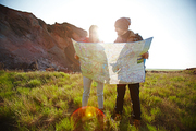 Young tourist couple, man and woman, on hiking path in mountains, holding big map and finding way in nature on sunny day