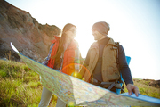 Lens flare image in bright sunlight of happy tourist couple, man and woman,  looking at each other while holding huge map on hiking path in mountains