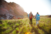 Back view image of young tourist couple traveling with big backpacks in nature, holding hands while walking by mountain path at sunset