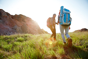 Couple traveling in mountains with big tourist backpacks, young man helping his girlfriend following him walk up the hiking path