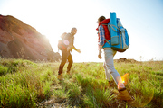 Active young couple traveling in mountains with big tourist backpacks, climbing uphill on green grass together on hiking path in bright sunlight