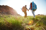 Romantic adventure of young tourist couple, low angle of man and woman going uphill holding hands towards bright sunlight on hike in nature