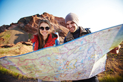 Portrait of young happy couple of adventurers holding huge map and finding their route on hiking path in mountains in bright sunlight
