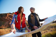 Low angle portrait of young cheerful couple holding huge map and looking at each other on hiking path in mountains lit by bright sunlight