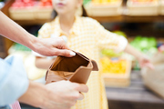 Close-up of unrecognizable woman opening empty brown wallet and finding money in supermarket