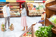 Outraged young couple in casual clothing standing in healthy food shop and gesturing while   fighting, they confronting with each other, shopping bags in floor