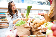 Serious concentrated attractive young woman in denim jacket crouching near food stall and putting products into bags, she taking care of her health and buying organic food