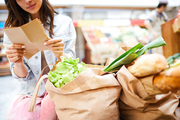 Close-up of content young woman crouching near full shopping bags and reading shopping list in organic food store