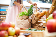 Close-up of unrecognizable woman in skirt standing in food organic store and picking heavy shopping bags full of products