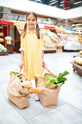 Smiling cute girl wearing yellow checkered dress holding handles of two big bags full of food, she enjoying shopping in farmers market