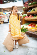 Cheerful excited girl in yellow checkered dress looking up and carrying full shopping bags in farmers market