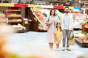 Positive beautiful young family in casual clothing standing in farmers market and holding shopping bags while looking at camera
