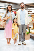 Smiling beautiful young family in casual outfits standing in supermarket and looking at camera, they doing shopping together