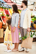Young family in casual clothing standing at fresh food stall full of fruits and vegetables and choosing healthy food in farmers market