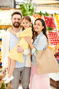 Optimistic young family in casual clothing standing against food stall and looking at camera, they enjoying shopping together in supermarket
