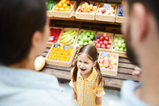 Upset hysterical girl with closed eyes crying loudly while manipulating parents and standing against food stall in supermarket