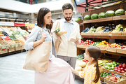 Little daughter pulling mothers skirt  while asking to buy something in food store, serious parents listening to her request