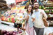 Positive beautiful young couple in casual clothing standing at farmers market and looking at camera, while paying money for purchase