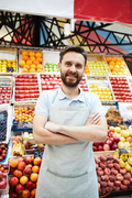 Content handsome young grocery retailer with beard wearing apron standing against fresh food shelves and smiling at camera while crossing arms on chest