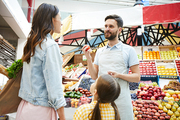 Content handsome young grocer in apron talking to customer and recommending to buy peach while selling fresh food at farmers market