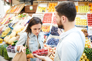 Puzzled frowning young female customer with shopping bag on shoulder displeased with quality of products and looking at strawberry shown by grocer in farmers market