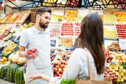 Confused misunderstanding young male grocer in apron holding container of strawberries shrugging shoulders while talking to customer in farmers market