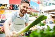 Cheerful handsome male grocer in apron putting leeks on shelf while placing new supply of products in farmers market