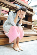 Upset attractive young woman in casual clothing concentrated on thoughts sitting on wooden stall and holding head in hands, bankruptcy concept