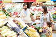 Young family buying fresh food at market: handsome bearded father asking wife while choosing vegetables, curious daughter listening to parents talk