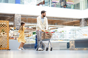 Dancing daughter walking with father over supermarket, positive handsome bearded man pushing shopping cart with bags and looking around
