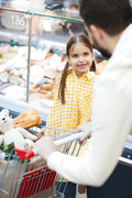 Cheerful excited pretty daughter in dress smiling while chatting with father pushing shopping cart in supermarket
