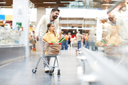 Serious cute girl sitting in shopping cart and pointing with finger at shelf while helping father with shopping in supermarket