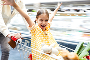 Jolly excited girl in checkered dress sitting in shopping cart and outstretching arms while having fun and looking at camera in supermarket, she riding in shopping cart