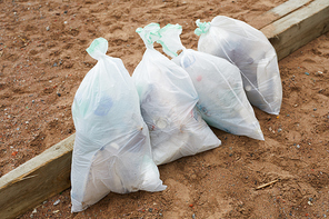 Ecology organization workers picking litter from dirty territory and utilizing it into special sacks