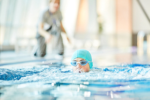 Young guy in swimwear swimming in water during sports competition