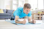 Young active man in blue t-shirt doing planks on the floor of living-room at home