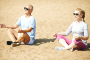 Contemporary senior couple in activewear and sunglasses sitting on sand in pose of lotus after workout