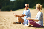 Senior man and his wife in activewear meditating on sand after morning workout