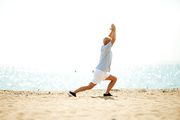 Active retired man in sportswear stretching legs and keeping his raised hands together while exercising on the beach