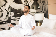 Young man in white sitting on bed in pose of lotus, concentrating and meditating before work