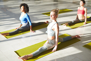 Group of fit girls in activewear performing twine on mats during workout in gym or yoga center