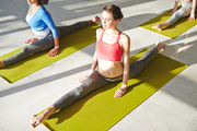 Young woman and her groupmates sitting in twine on mats in fitness or yoga center