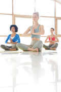 Young yoga instructor and two girls in activewear meditating the floor in pose of lotus